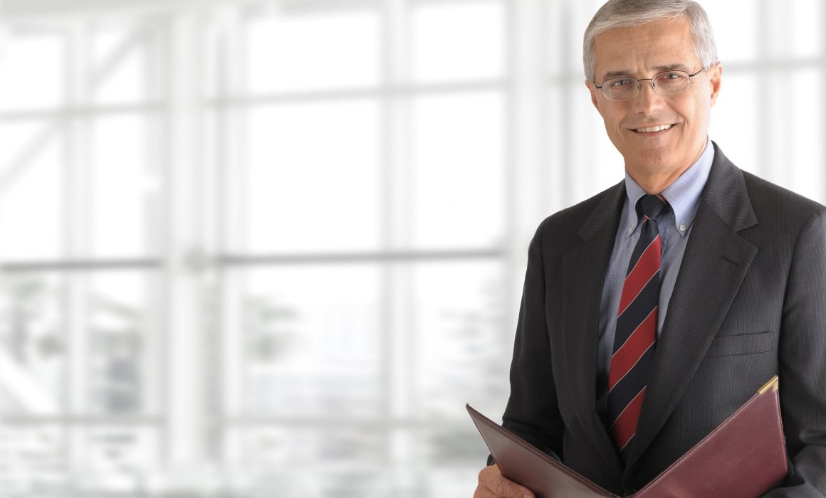 Mature smiling business manager holding a folder while standing in front of a large office window. Horizontal format with copy space.