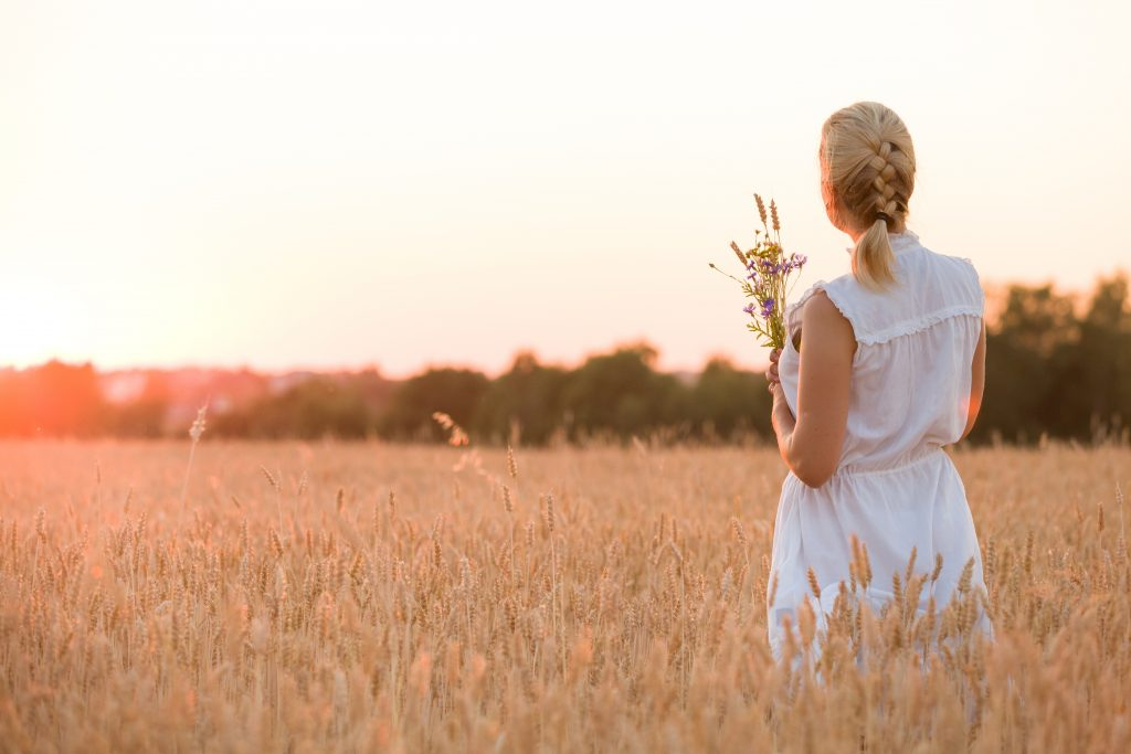 Back view on blond woman with flowers mourning her recently deceased husband on a wheat field on sunset. Outdoors.